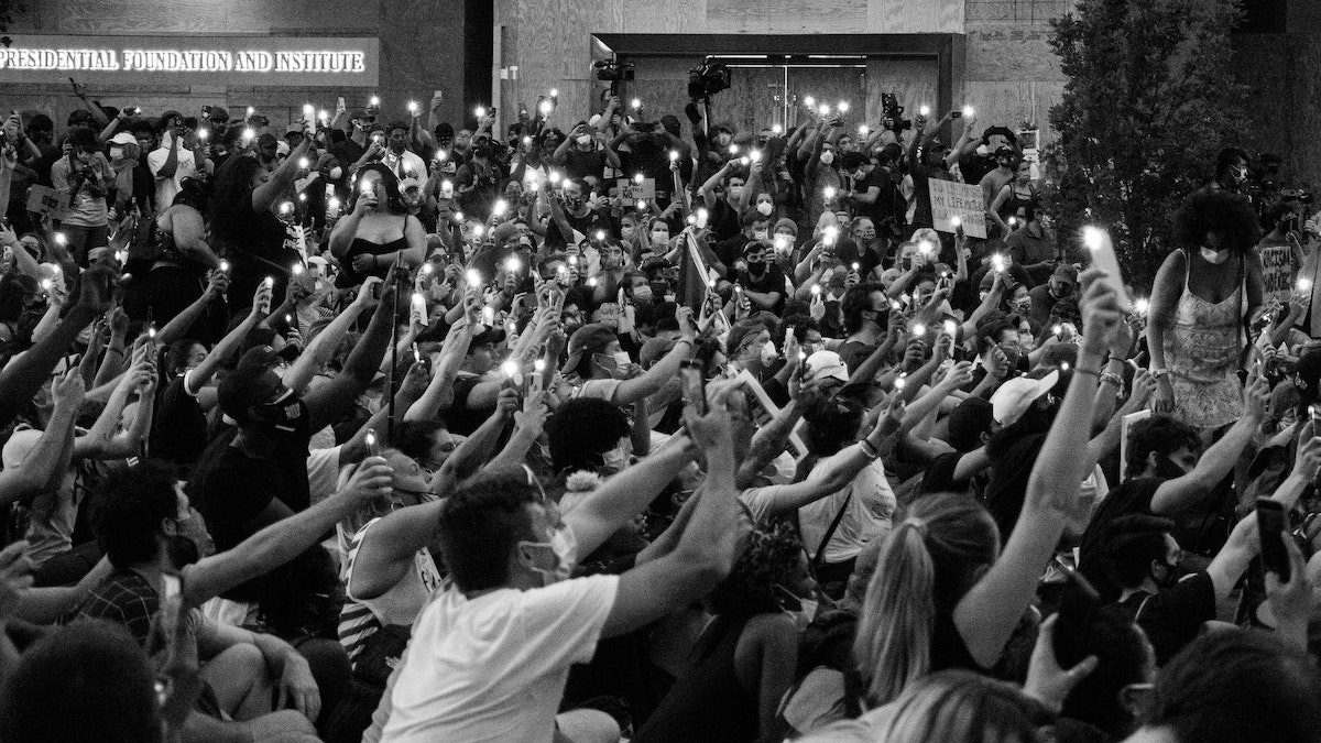 Photo of people holding up phones at protest